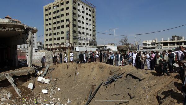 Yemenis gather around a crater caused by a Saudi-led airstrike that targeted a building in the centre of the capital Sanaa (File) - Sputnik International