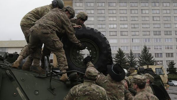 US army soldiers roll a tyre from top of a stryker armored vehicle during a stop of his convoy in Prague, Czech Republic, Tuesday, March 31, 2015 - Sputnik International