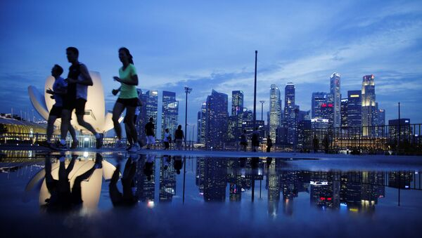 Joggers run past as the skyline of Singapore's financial district is seen in the background - Sputnik International
