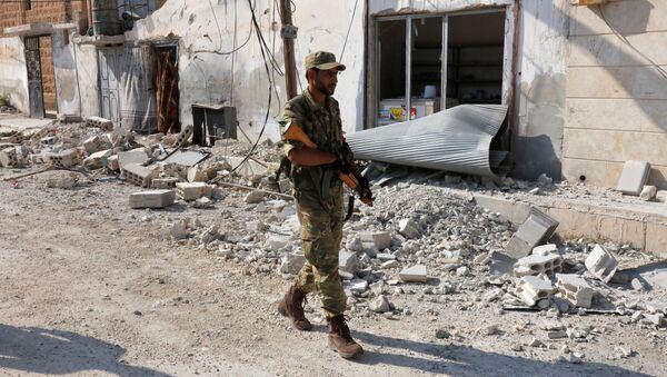 A member of Turkish-backed Free Syrian Army (FSA) patrols in the border town of Jarablus, Syria - Sputnik International