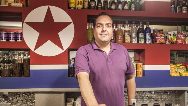 Alejandro Cao de Benós poses in Café Pyongyang with North Koeran flag on the background - Sputnik International