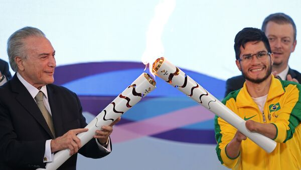 Brazil's acting President Michel Temer, left, lights the torch of Paralympic athlete Yohansson Nascimento during a ceremony for 2016 Rio Paralympic Games at the Planalto Presidential Palace, in Brasilia, Brazil, Thursday, Aug. 25, 2016. - Sputnik International