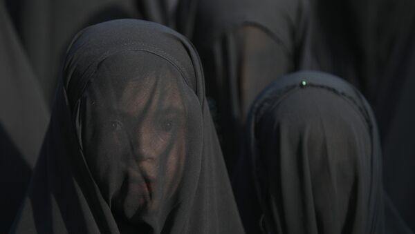 An Iraqi Shiite girl, whose face is covered with a veil, takes part in a parade in preparation for the peak of the mourning period of Ashura in Baghdad's northern district of Kadhimiya on October 22, 2015 - Sputnik International