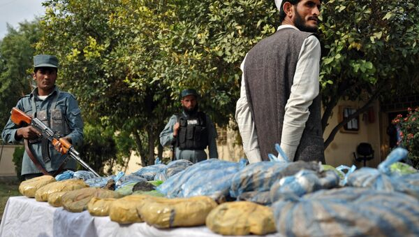 An Afghan policeman (L) stands guard as a detained suspect and bags containing heroin are presented to the media at a police station in Jalalabad on November 17, 2012. - Sputnik International