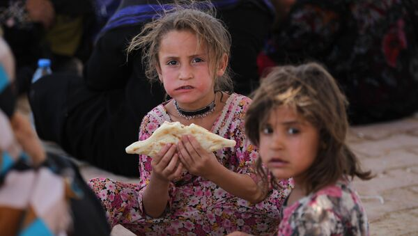 Iraqi civilians gather on July 27, 2016 at a camp for displaced people in the district of Hajaj after fleeing the villages of al-Shirqat and Qayyarah south of the city of Mosul during reported fighting between Iraqi security forces and the Islamic State (IS) group - Sputnik International
