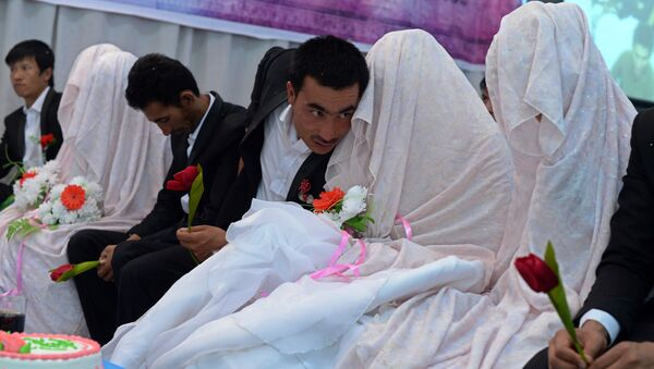 In this photograph taken on October 10, 2014, an Afghan groom (C) talks with his bride during a mass wedding ceremony in which one hundred couples were married on the outskirts of Kabul - Sputnik International