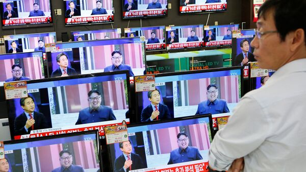 A sales assistant watches TV sets broadcasting a news report on North Korea's fifth nuclear test, in Seoul, South Korea, September 9, 2016. - Sputnik International