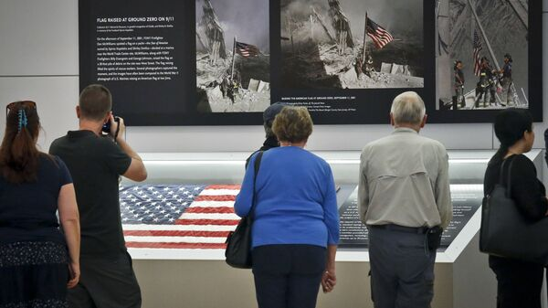Visitors view the display for the American flag, left, that firefighters hoisted at ground zero in the hours after the 9/11 terror attack  at the Sept. 11 museum in New York - Sputnik International
