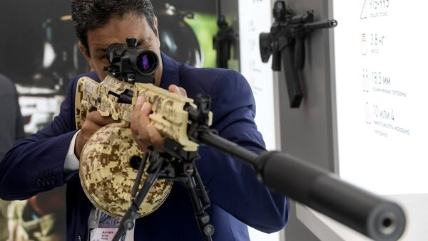 A visitor reviews an RPK-16 light machine rifle at the Kalashnikov pavilion, at the ARMY 2016 International Military Forum, at the exhibition center of the Patriot Military Park of the Russian Armed Forces in the Moscow Region. - Sputnik International