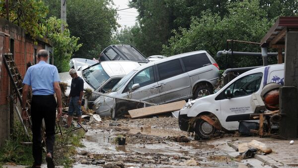 People walk through a street where cars have piled due to overnight flooding, after storms in the village of Stajkovci, just east of Skopje, Macedonia, Sunday, Aug. 7, 2016. - Sputnik International