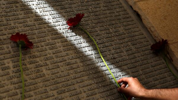 A man lays a flower on a monument engraved with names of victims of the September 11th attacks, during a memorial event marking the 15th anniversary of September 11, 2001 attacks in the U.S., at the 9/11 Living Memorial Plaza in Jerusalem - Sputnik International