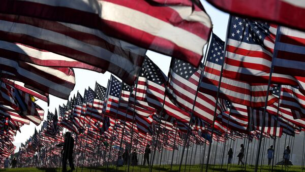 People walk amongst US national flags erected by students and staff from Pepperdine University as they pay their respects to honor the victims of the September 11, 2001 attacks in New York, at their campus in Malibu, California - Sputnik International