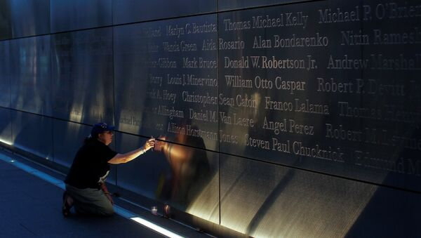 A mourner places a flag in the Empty Sky memorial on the morning of the 15th anniversary of the 9/11 attacks in New Jersey, U.S - Sputnik International