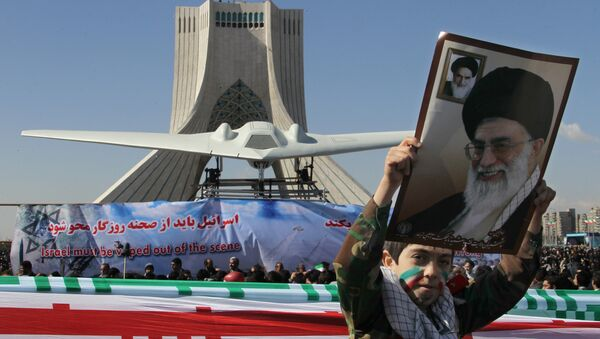An Iranian boy holds a portrait of supreme leader, Ayatollah Ali khamenei as he walks past a replica of the captured US RQ-170 drone on display next to the Azadi (Freedom) tower during the 33rd anniversary of the Islamic revolution in Tehran on February 11, 2012 - Sputnik International
