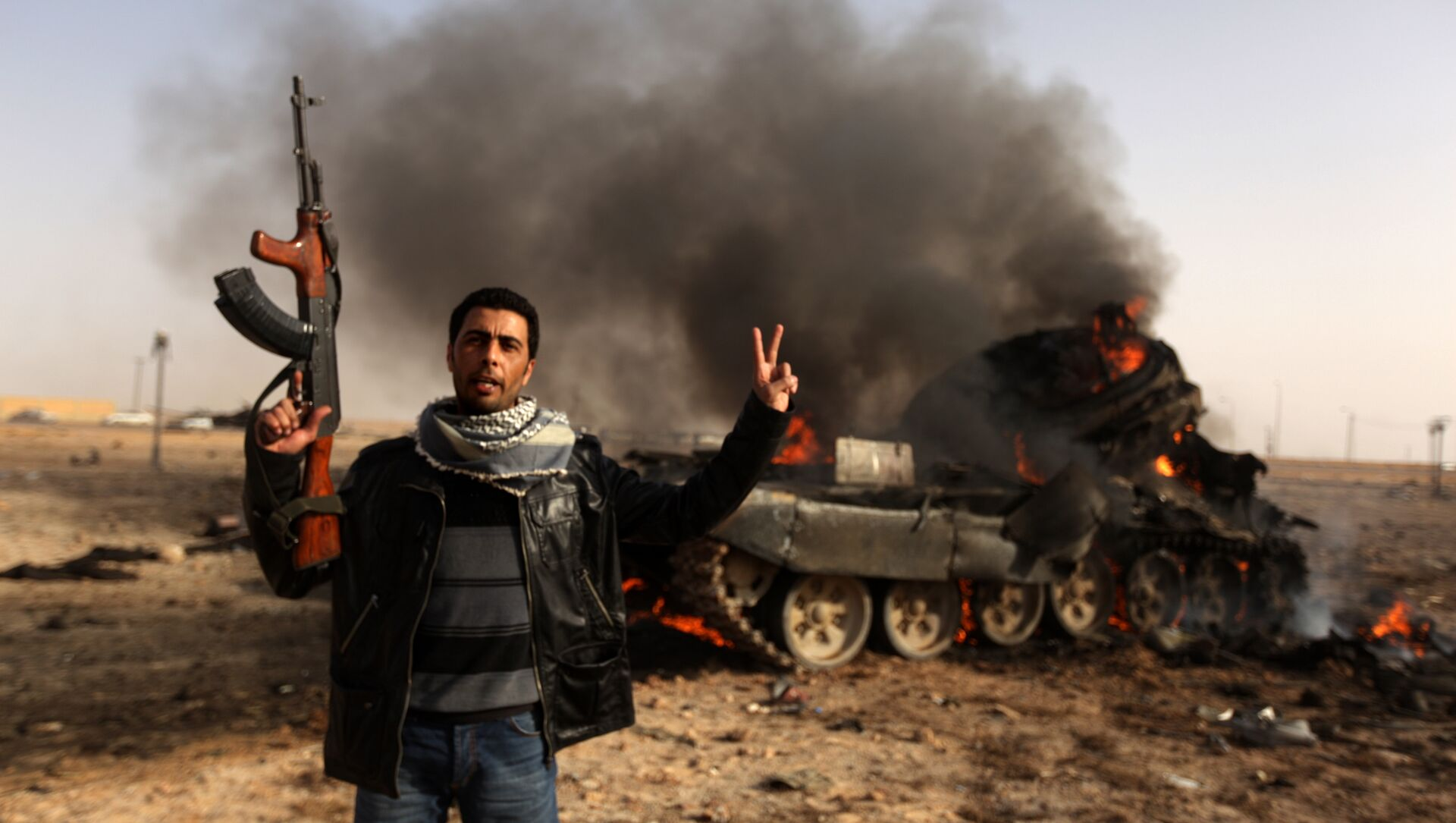 A Libyan rebel flashes a V-sign in front of burning tank belonging to loyalist forces bombed by coalition air force in the town of Ajdabiya on March 26, 2011 - Sputnik International, 1920, 15.02.2021
