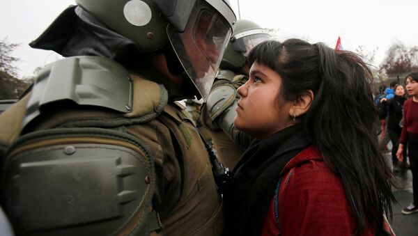A demonstrator looks at a riot policeman during a protest marking the country's 1973 military coup in Santiago, Chile September 11, 2016.  - Sputnik International