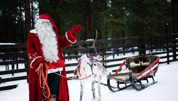 Santa Claus waves as he stands with a reindeer and sled outside Rovaniemi, Finnish Lapland on December 15, 2011 - Sputnik International