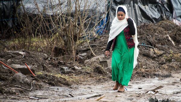 A migrant woman walks along a muddy path in the so-called Jungle refugee and migrant camp in Calais, on February 24, 2016. - Sputnik International