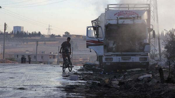 A boy rides a bicycle near a damaged aid truck after an airstrike on the rebel held Urm al-Kubra town, western Aleppo city, Syria September 20, 2016. - Sputnik International