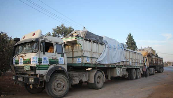 Trucks carrying aid are seen on the side of the road in the town of Orum al-Kubra on the western outskirts of the northern Syrian city of Aleppo on September 20, 2016, the morning after a convoy delivering aid was hit by a deadly air strike - Sputnik International