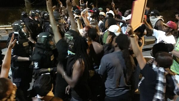 Protestors demonstrate in front of police officers wearing riot gear after police fatally shot Keith Lamont Scott in the parking lot of an apartment complex in Charlotte, North Carolina, U.S. September 20, 2016 - Sputnik International