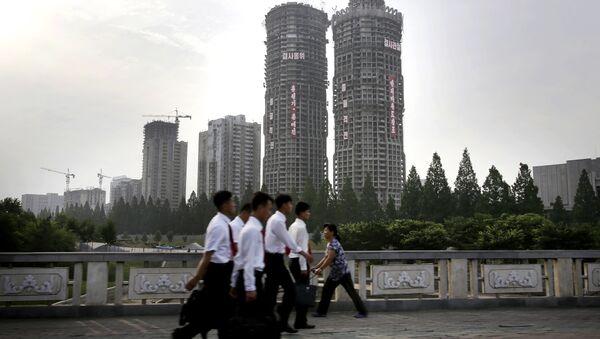 "In this June 27, 2016, photo, North Korean men and women walk past buildings under construction on ""Ryomyong Street,"" in Pyongyang, North Korea - Sputnik International"
