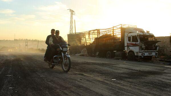 Men drive a motorcycle near a damaged aid truck after an airstrike on the rebel held Urm al-Kubra town, western Aleppo city, Syria September 20, 2016 - Sputnik International