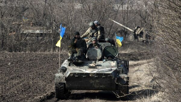 Ukrainian servicemen ride atop armored vehicle with a canon in tow and Ukrainian flags, near the village of Fedorivka, eastern Ukraine, Friday, Feb. 27, 2015 - Sputnik International