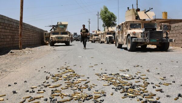 Shell casings lie on the ground as Iraqi government forces gather around the Qayyarah airbase, which was seized by Iraqi forces last week from jihadists of the Islamic State (IS)group, on July 13, 2016, some 60 kilometres (35 miles) south of Mosul - Sputnik International