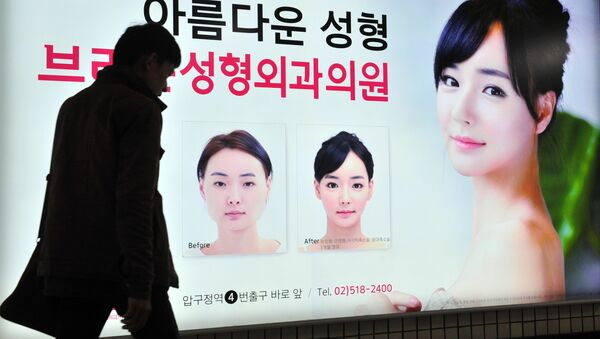 A pedestrian walks past an advertisement for plastic surgery clinic at a subway station in Seoul on March 26, 2014 - Sputnik International