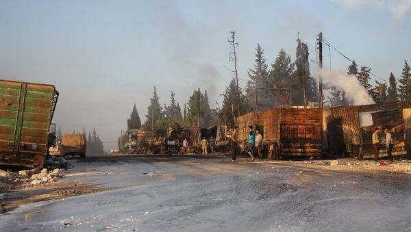 Syrians gather near damaged trucks carrying aid on the side of the road in the town of Orum al-Kubra on the western outskirts of the northern Syrian city of Aleppo on September 20, 2016, the morning after a convoy delivering aid was hit by a deadly air strike - Sputnik International
