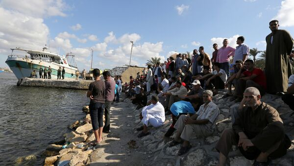 People gather along the shore of the Mediterranean Sea during a search for victims after a migrant boat capsized, in Al-Beheira, Egypt, September 22, 2016 - Sputnik International