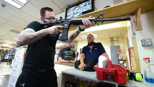 LAX Firing Range employee Tommy Bushnell demonstrates how to use an AR15 rifle to gun enthusiasts waiting to shoot at targets in Inglewood, California on September 7, 2016 - Sputnik International