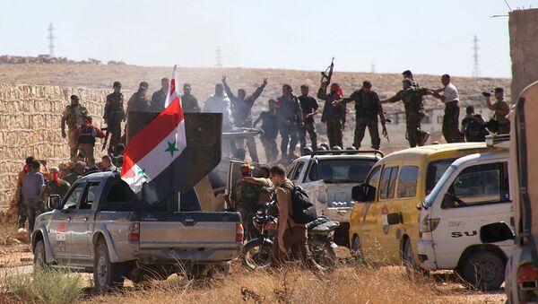 Syrian government forces celebrate in the largely deserted Palestinian refugee camp of Handarat, north of Aleppo, on September 24, 2016 - Sputnik International
