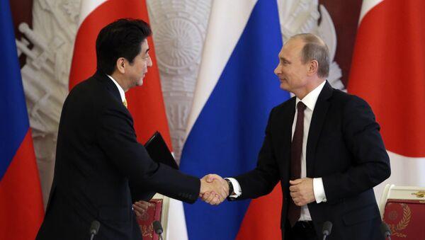 Japanese Prime Minister Shinzo Abe (L) shakes hands with Russian President Vladimir Putin - Sputnik International