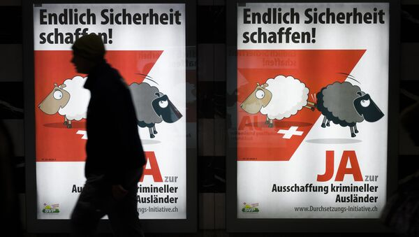 A man walks past backlit posters of the right-wing populist Swiss People's Party (SVP) that translate from German as Finally Create Security to advertise their initiative for the eviction of criminal foreigners in Zurich on February 25, 2016. - Sputnik International