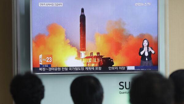 People watch a TV news channel airing an image of North Korea's ballistic missile launch published in North Korea's Rodong Sinmun newspaper at the Seoul Railway Station in Seoul. (File) - Sputnik International