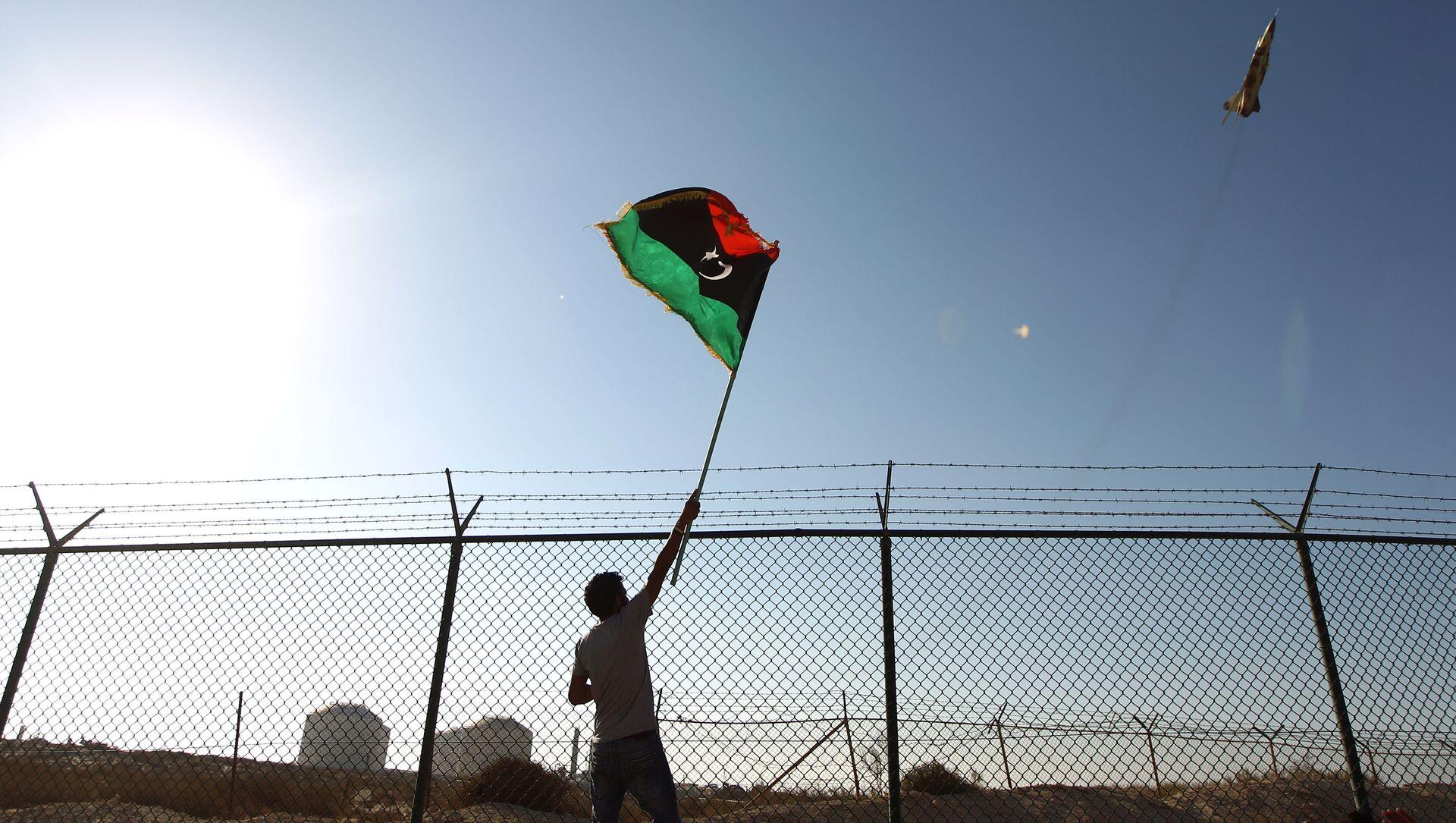 A man waves a Libyan flag - Sputnik International, 1920, 15.02.2021