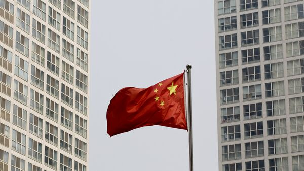 A Chinese national flag flutters in the wind in between a high-rise residential and office complex in Beijing, China. (File) - Sputnik International