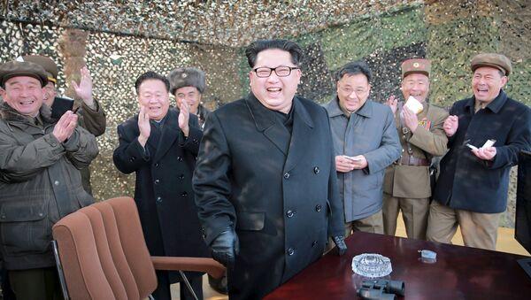 North Korean leader Kim Jung Un smiles after a successful test of a new rocket launch system. - Sputnik International