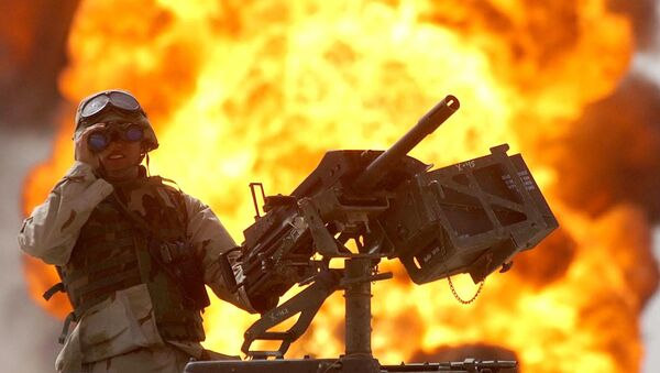 A US soldier looks through a pair of binoculars as a fire in the Rumeila oil field burns in the background in southern of Iraq, Sunday, March 30, 2003. - Sputnik International