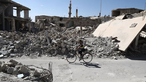 A Syrian boy rides a bicycle past destroyed buildings in the rebel-held town of Douma, on the eastern outskirts of the capital Damascus on September 25, 2016 - Sputnik International
