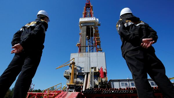 Workers look at a drilling rig at a well pad of the Rosneft-owned Prirazlomnoye oil field outside the West Siberian city of Nefteyugansk, Russia, August 4, 2016 - Sputnik International