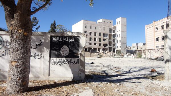 A general view taken on September 25, 2016 shows the flag of the Islamic State (IS) group painted on the wall outside the ancient Minbij hotel in the Syrian town of Manbij, that was used as a prison when it was under the control of the Islamic State (IS) group. - Sputnik International
