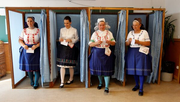 Hungarian women wearing traditional costume leave a voting booth at a polling station during a referendum on EU migrant quotas in Veresegyhaz, Hungary, October 2, 2016. - Sputnik International