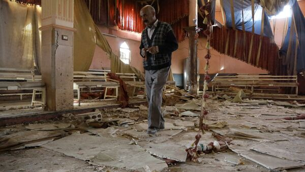 A man inspects the damage at a wedding hall a day after a suicide attack targeted a Kurdish wedding party in the village of Tall Tawil in the Syrian Hasakeh province - Sputnik International