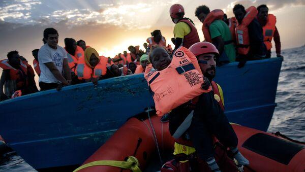 Спасение ребенка с терпящего бедствие судна с мигрантами в Средиземном море - Sputnik International