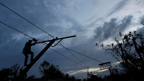 A worker for an electricity company fixes a power line affected by Hurricane Matthew on the outskirts of Les Cayes, Haiti, October 6, 2016 - Sputnik International