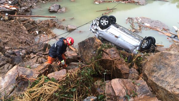 A rescue worker is seen next to an overturned car at the site of a landslide caused by heavy rains brought by Typhoon Megi, in Sucun Village, Lishui, Zhejiang province, China, September 29, 2016 - Sputnik International