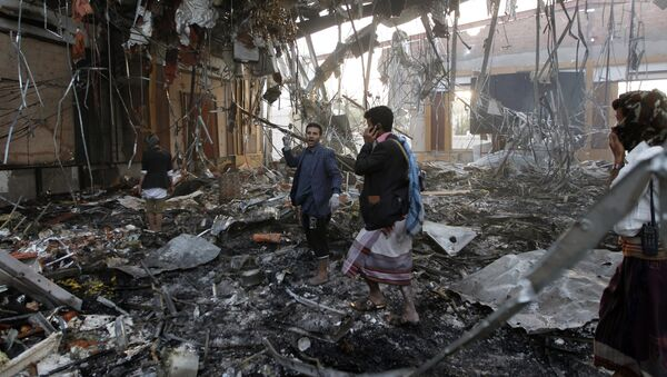 Yemeni rescue workers search for victims amid the rubble of a destroyed building following reported airstrikes by Saudi-led coalition air-planes on the capital Sanaa on October 8, 2016 - Sputnik International